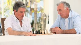 Senior friends men playing chess stock footage