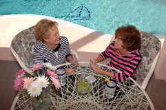 Senior friends playing cards. On a patio beside a pool (view from above Stock Photography