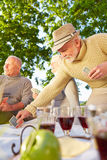 Senior friends playing cards in a garden Royalty Free Stock Image