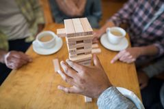 Senior friends playing jenga game on table in bar. Mid section of senior friends playing jenga game on table in bar Royalty Free Stock Photo