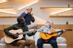 Senior friends playing music. Group of senior friends playing music with guitars and harmonica in modern public cafe stock image