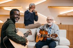 Senior friends playing music. Mutiethnic group of senior friends playing music with guitars and harmonica Royalty Free Stock Images