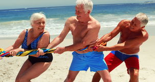 Senior friends playing tug of war stock footage