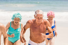 Senior friends running together. On the beach Stock Image