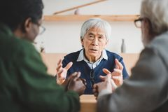 Senior friends sharing stories. Group of multiethnic senior friends spending time together and sharing stories from past Stock Image