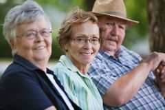 Senior friends sitting together in park. Portrait of senior friends sitting together in park Royalty Free Stock Image