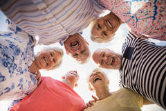 Senior friends standing in circle. On the beach Stock Photography