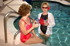 Senior friends summer. Senior friends in a swimming pool at a tropical location Royalty Free Stock Images