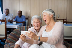 Senior friends taking selfie through smart phone. While sitting on sofa at nursing home Royalty Free Stock Photography