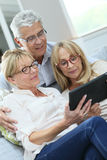 Senior friends using tablet at home royalty free stock image