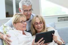 Senior friends using tablet at home royalty free stock images