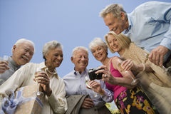 Senior Friends Watching Recorded Moments Together Royalty Free Stock Images