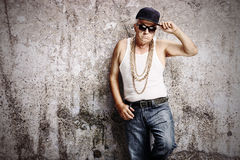 Senior gangster leaning against a rusty wall Stock Photography
