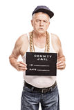 Senior gangster posing for a mug shot. Vertical shot of a senior gangster in a hip hop outfit posing for a mug shot isolated on white background Stock Images