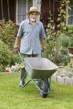 Senior in the garden. Senior posing with a wheelbarrow  in the garden Stock Image