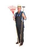 Senior gardener with equipment. Senior gardener standing in studio with garden equipment royalty free stock images