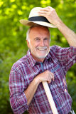 Senior gardener greets with hat Royalty Free Stock Photo
