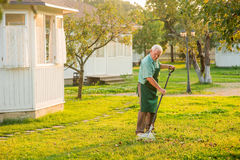 Senior gardener with rake. Old man in apron outdoors stock photos