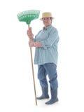 Senior gardener with rake. Senior woman gardener wearing straw hat and rubber boots posing with rake over white background stock photography