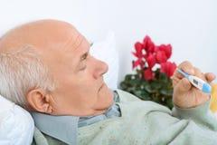 Senior gentelman checks the thermometer with a Royalty Free Stock Photos