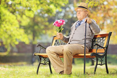 Senior gentleman with bunch of flowers sitting on a bench, in a Stock Photography