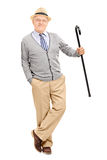 Senior gentleman with cane, leaning against a wall Royalty Free Stock Photo
