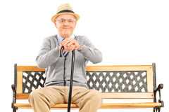 Senior gentleman with a cane sitting on bench. Isolated on white background Royalty Free Stock Image