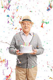 Senior gentleman carrying a birthday cake Royalty Free Stock Photography