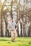 Senior gentleman dancing out of joy in the park Royalty Free Stock Image