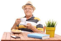 Senior gentleman drinking coffee seated at a table Stock Photography