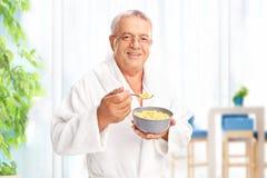 Senior gentleman eating cereal at home. Senior gentleman in a white bathrobe eating cereal at home from a gray bowl and looking at the camera stock photos