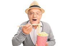 Senior gentleman eating Chinese food with sticks stock photo