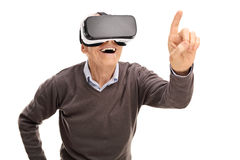 Senior gentleman experiencing virtual reality. And reaching to touch something with his finger isolated on white background Stock Photos