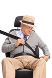 Senior gentleman fastening a seatbelt Stock Photos