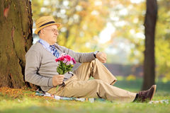 Senior gentleman with flowers checking the time, in a park Stock Image