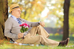 Senior gentleman with flowers sitting on grass and checking the Stock Photos