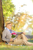 Senior gentleman with flowers sitting on a grass and checking th Royalty Free Stock Photos