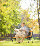 Senior gentleman with hat on bench and reading a newspaper in a Stock Image