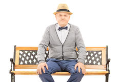 Senior gentleman with hat seated on bench looking at camera Stock Images