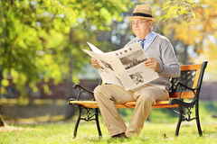 Senior gentleman with hat sitting on a bench and reading a newsp Stock Photo