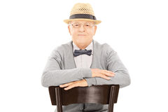 Senior gentleman with hat sitting on a chair Stock Image