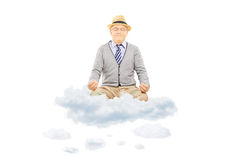 Senior gentleman with hat sitting on clouds and meditating Royalty Free Stock Photography