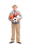 Senior gentleman holding a bunch of sports balls Royalty Free Stock Photos