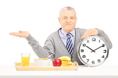 Senior gentleman holding a clock and gesturing Royalty Free Stock Images