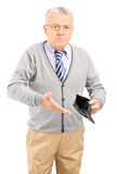 Senior gentleman holding an empty wallet Royalty Free Stock Image