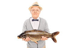 Senior gentleman holding a freshwater fish Stock Images