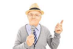 Senior gentleman holding microphone and pointing up with finger Stock Images