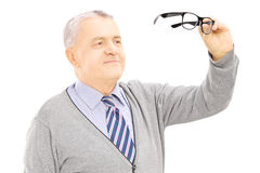 Senior gentleman holding a pair of glasses Stock Photos