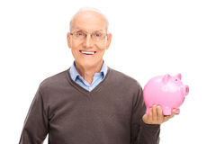 Senior gentleman holding a pink piggybank. Cheerful senior gentleman holding a pink piggybank and looking at the camera isolated on white background Royalty Free Stock Image