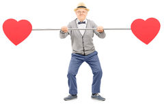 Senior gentleman holding a pipe with hearts on both ends Royalty Free Stock Images